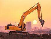 image of risen  - heavy wheel excavator machine working at sunset - JPG