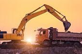 stock photo of backhoe  - heavy wheel excavator machine working at sunset - JPG