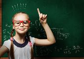 picture of formulas  - Genius girl in red glasses near blackboard with formulas - JPG