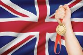 Medal In Hand With Flag On Background - United Kingdom Of Great Britain And Northern Ireland