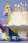 Birthday still life of cake on stand with multiple colored lit candles on blue background
