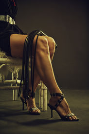 picture of scourge  - Mistress sitting on a chair with lash over dark background - JPG