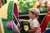 stock photo of arcade  - Boy playing arcade game machine at an amusement park - JPG
