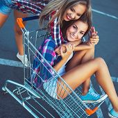 picture of adoration  - Two happy beautiful teen girls driving shopping cart outdoors lifestyle concept - JPG