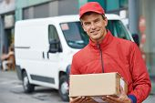 stock photo of packages  - Smiling male postal delivery courier man outdoors  in front of cargo van delivering package - JPG