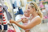 foto of apparel  - woman choosing children apparel with little baby child on hands in clothing shop supermarket - JPG