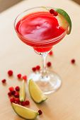 image of cosmopolitan  - cosmopolitan cocktail garnished with a lime and berries - JPG