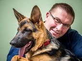 stock photo of shepherd  - Happy young man posing with its German shepherd pet - JPG