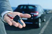 stock photo of courtesy  - man in suit offering a car key to the observer - JPG