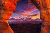 picture of arch  - La Sal Mountains as seen through Delicate Arch on a colorful late afternoon in Arches National Park Utah - JPG