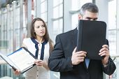 picture of coworkers  - Businessman hides from coworker behind folder - JPG