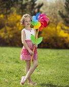 stock photo of wind wheel  - Young girl holding large Flower shaped wind wheel - JPG