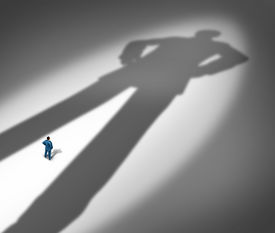 stock photo of competing  - Under a shadow business metaphor for living under a powerful leader or the little guy or small business competing against giants as a businessman facing a huge darkness shaped as a giant man as a symbol of a bodyguard or guardian angel - JPG