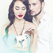 picture of enamored  - Fashion photo of beautiful romantic couple with gift - JPG