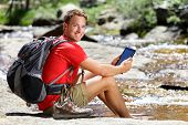 stock photo of usa map  - Tablet computer man hiker relaxing by river holding ebook reader reading e book or map - JPG