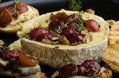 stock photo of vinegar  - Brie cheese baked with nuts and grapes tasty and crispy baguette and bio herbs reduction of sugar nuts and balsamic vinegar - JPG