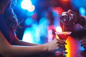pic of cocktail  - Young woman holding martini glass while barman pouring cocktail - JPG