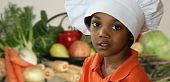 image of chefs hat  - Happy little chef standing in front of a variety of vegetables.