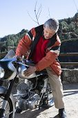 stock photo of caress  - portrait of a middle aged man sitting on his classic motorcycle and caressing the fuel tank after its restoration  - JPG