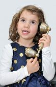 pic of babbler  - Cute young girl wearing a blue dress with gold spots talking on the retro telephone - JPG