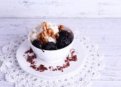 stock photo of doilies  - Dessert with prunes and nuts in cup on lace doily on color wooden background - JPG