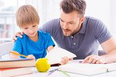 picture of homework  - Confident young father helping his son with homework while sitting at the table together - JPG