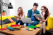 pic of couch  - Three young friends or students working with digital gadgets on the yellow couch at home - JPG
