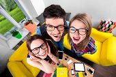 pic of nerds  - Three funny nerds looking together at camera standing in the room with couch and different digital stuff on background - JPG