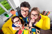 stock photo of nerds  - Three funny nerds looking together at camera standing in the room with couch and different digital stuff on background - JPG