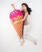 pic of sweet dreams  - Top view photo of young woman sleeping in an embrace with a large soft ice cream toy and dreaming of sweets - JPG