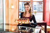 foto of confectioners  - Female confectioner presenting tray of cake in bakery or pastry shop - JPG