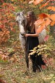 stock photo of appaloosa  - Pretty young woman with appaloosa horse in autumn