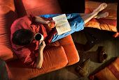 picture of reading book  - Man is lying on the couch and reading a book - JPG