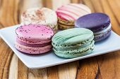 stock photo of dessert plate  - french macaroons on a white plate in a variety of colors an d flavors