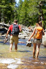 stock photo of barefoot  - Hikers group walking barefoot crossing river in forest - JPG