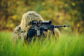 picture of sniper  - Sniper in the grass looking through the scope  - JPG