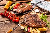 Постер, плакат: Beef steaks with grilled vegetables and seasoning on wooden background