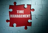 picture of time-piece  - Missing pieces from a jigsaw puzzle revealing time management - JPG