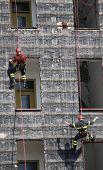 stock photo of firehouse  - rescuers during the workouts climbing the facade of a building - JPG