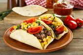 stock photo of tacos  - Mexican food Taco in clay plate on wooden table - JPG