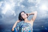 image of purity  - beautiful young woman on a background of sky and clouds expressing purity and freedom - JPG
