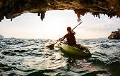 picture of cave woman  - Young lady paddling the kayak in a sea near the cave exit - JPG