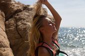 pic of wild adventure  - Adventure girl playing with her hair on the wild coast - JPG
