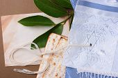 picture of matzah  - Matzah and a blue and white tallit laying next to an old piece of paper - JPG