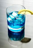 picture of curacao  - Glass Of Blue Curacao Cocktail With Slice Of Lemon - JPG