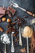 stock photo of chocolate spoon  - Sweet powdered ingredients in a spoon and chocolate on a table black - JPG