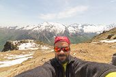 picture of italian alps  - Adult european hiker with sunglasses and beard taking selfie in springtime with the beautiful snowcapped italian Alps in the background - JPG
