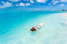 image of floating  - Woman floating and relaxing in turquoise waters at colorful tropical beach - JPG