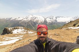 stock photo of italian alps  - Adult european hiker with sunglasses and beard taking selfie in springtime with the beautiful snowcapped italian Alps in the background - JPG