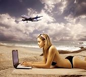 stock photo of sea-scape  - sexy girl using laptop against a sea scape with an airplane flying - JPG